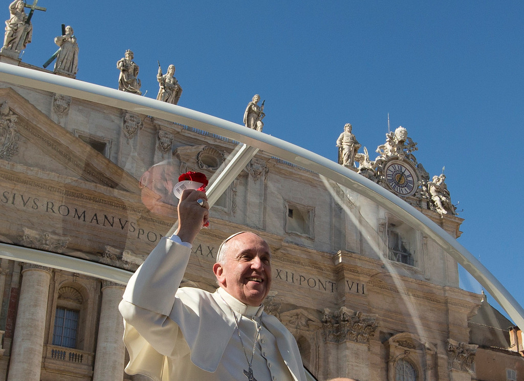 . Pope Francis holds a rose tossed by a faithful in St. Peter\'s Square at the Vatican, Friday, Feb. 14, 2014. Pope Francis met a group of engaged couples on Valentine\'s Day. (AP Photo/Alessandra Tarantino)