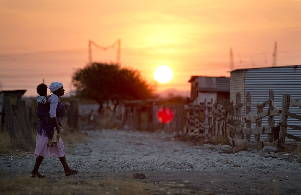 . A woman carries her child as the sun sets in the shanty town of Nkaneng next to Lonmin\'s platinum smelter in Marikana on July 9, 2013. Police opened fire on illegal strikers at the Lonmin platinum mine in Marikana, north west of Johannesburg on August 16 last year, a move that led to 34 people being shot dead. Strikers were asking for better wages and living conditions and despiste a small increase they still live in dire conditions. ODD ANDERSEN/AFP/Getty Images