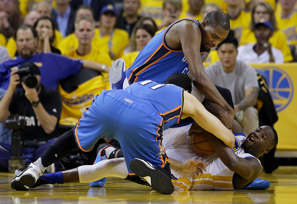 . Golden State Warriors forward Draymond Green, bottom right, holds onto the ball under Oklahoma City Thunder center Enes Kanter (11) and forward Kevin Durant during the first half of Game 2 of the NBA basketball Western Conference finals in Oakland, Calif., Wednesday, May 18, 2016. (AP Photo/Marcio Jose Sanchez)