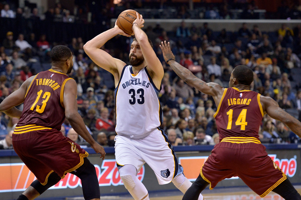 . Memphis Grizzlies center Marc Gasol (33) controls the ball between Cleveland Cavaliers center Tristan Thompson (13) and guard DeAndre Liggins (14)in the second half of an NBA basketball game Wednesday, Dec. 14, 2016, in Memphis, Tenn. (AP Photo/Brandon Dill)