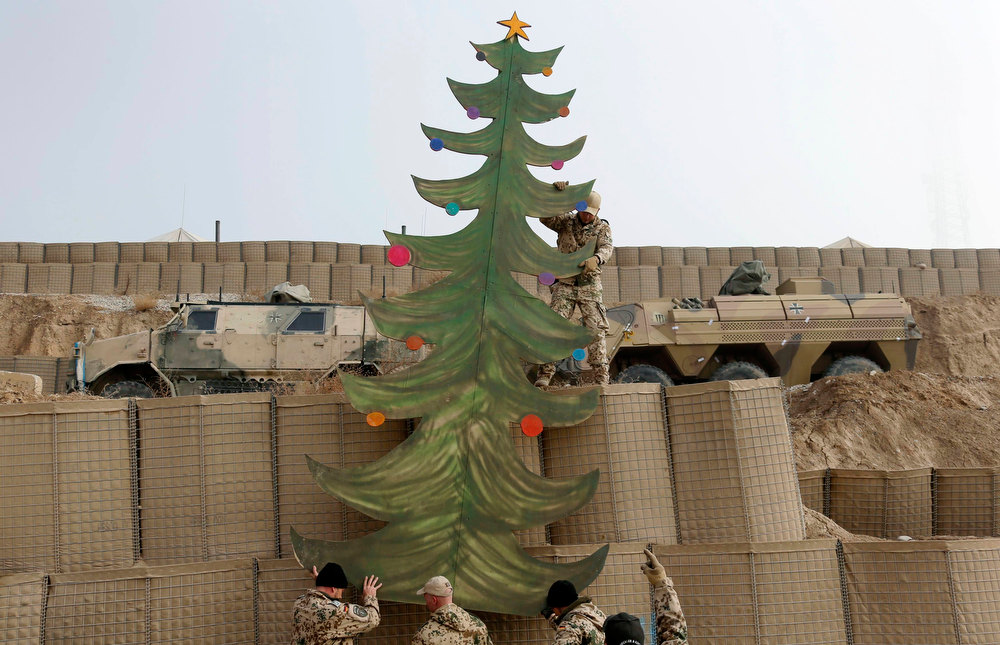 Description of . German Bundeswehr army soldiers set up a self-painted Christmas tree for a Christmas market at their combat outpost OP North, near Baghlan, northern Afghanistan December 9, 2012. German soldiers celebrate their last Christmas at their combat outpost OP North this year before it is removed in 2013. REUTERS/Fabrizio Bensch
