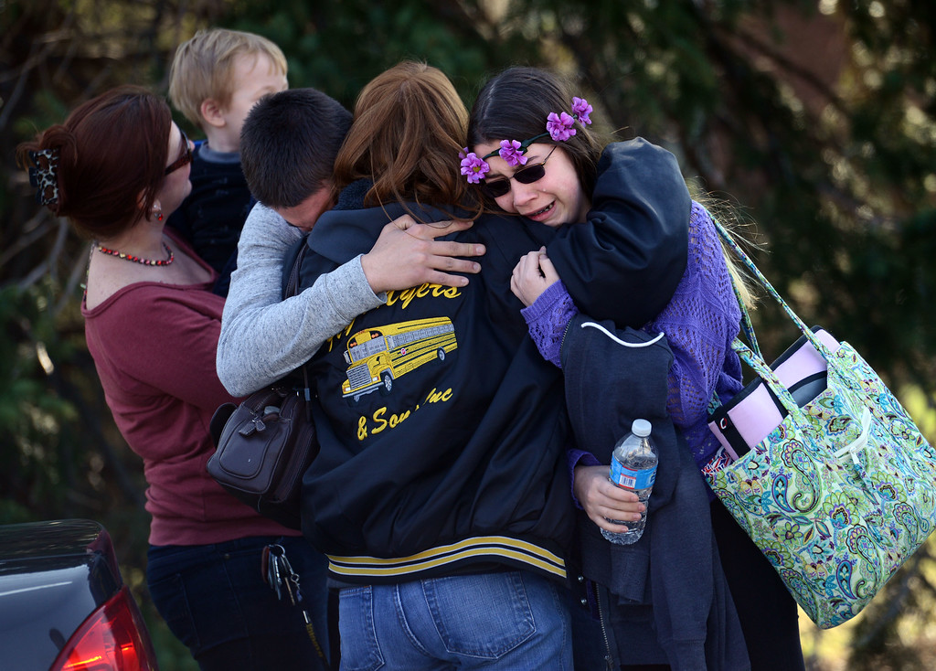 . Parents and students embrace along School Road near Franklin Regional High School after more than a dozen students were stabbed by a knife wielding suspect at the school on Wednesday, April 9, 2014, in Murrysville, Pa., near Pittsburgh. The suspect, a male student, was taken into custody and is being questioned. (AP Photo/Tribune Review, Sean Stipp)