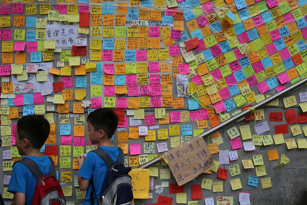 ". Children stand in front of a wall filled with sticky notes supporting the democratic movement near the Hong Kong government headquarters on October 2, 2014.  Tensions in Hong Kong soared after police were seen unloading boxes of tear gas and rubber bullets close to the city\'s besieged government headquarters as the authorities urged pro-democracy demonstrators to disperse ""as soon as possible\"".    AARON TAMaaron tam/AFP/Getty Images"
