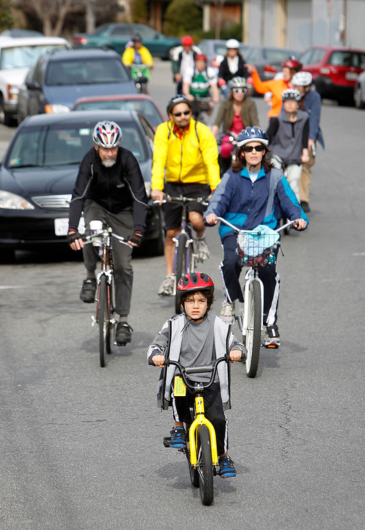 . Mateo Andrade, 6, leads a pack of bicyclists along Latham Street during the Great Streets Rengstorff Park Neighbor Bike Tour in Mountain View, Calif. on Sat., March 2, 2013. (LiPo Ching/Staff)