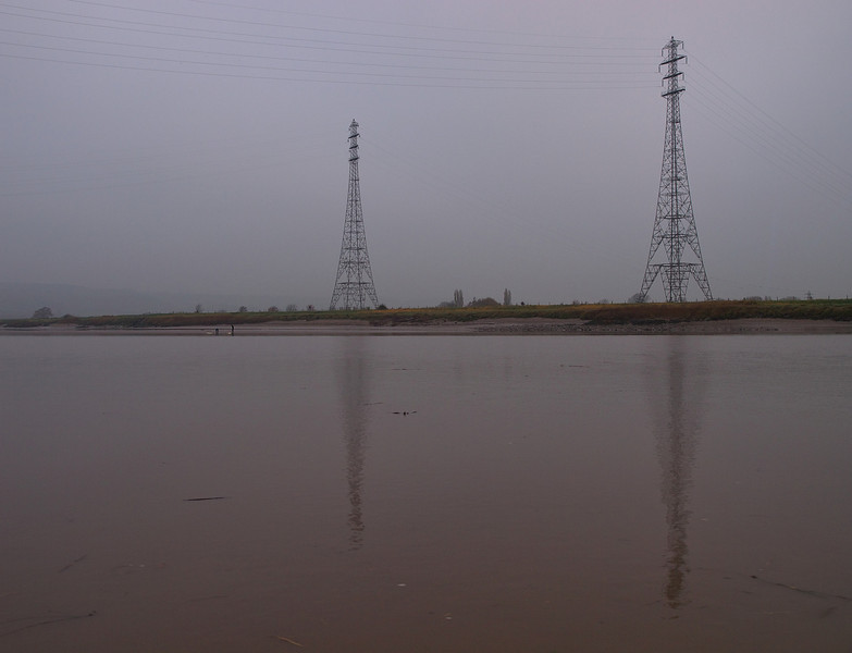 Surfers arrive on the river Severn early for the bore, dwarfed by the pylons. Nice reflections today.