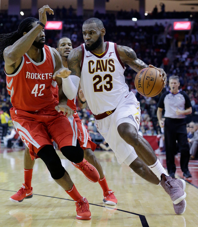 . Houston Rockets center Nene Hilario (42) defends as Cleveland Cavaliers forward LeBron James (23) drives around him during the first half of an NBA basketball game Thursday, Nov. 9, 2017, in Houston. (AP Photo/Michael Wyke)