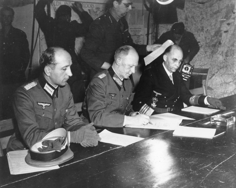 . General Alfred Jodl, center, signs the unconditional surrender of all armed German forces imposed by the Allied Powers, at Supreme Commander Eisenhowers headquarters in Rheims, France, on May 7, 1945. He is flanked by General Wilhelm Oxenius, Commander of the German Luftwaffe, left, and General Admiral and Commander in Chief of the German fleet, Hans-Georg von Friedeburg, right. (AP Photo)