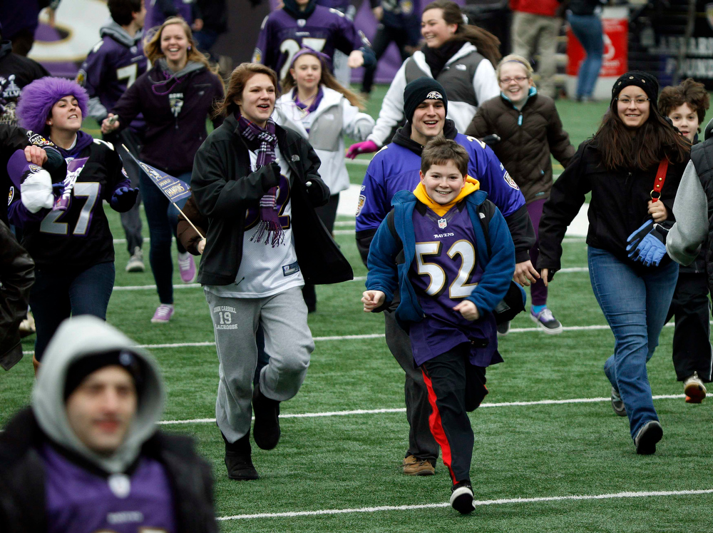 Description of . Fans of Super Bowl XLVII champion Baltimore Ravens run onto their home stadium's playing field before a rally in Baltimore February 5, 2013. The Ravens defeated the San Francisco 49ers to win the NFL championship.     REUTERS/Gary Cameron