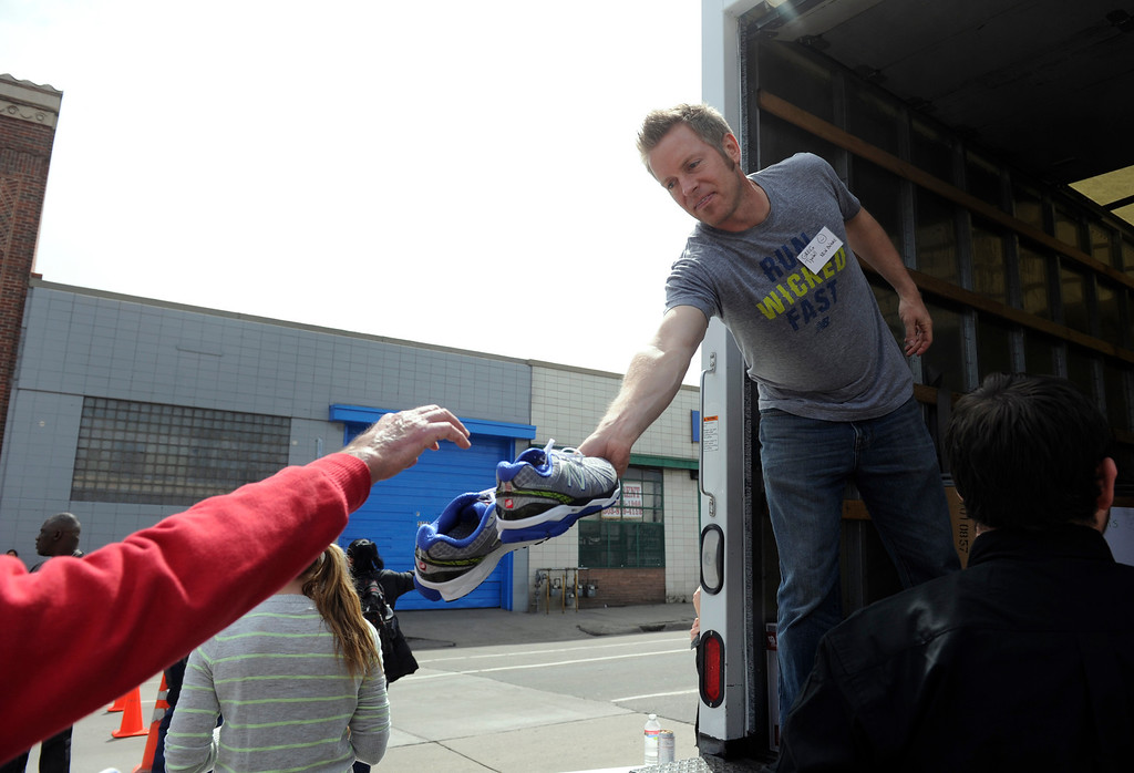 . DEVNER, CO.- MARCH 29: Volunteer Greg Tyndall hands off a pair of shoes to be given away. The Denver Rescue Mission partners with Volunteers of American and Runner\'s Roost to supply approximately 600 homeless adults and children with a new pair of shoes, sock and an Easter meal at the 20th Annual Easter Celebration  at the Rescue Mission on Lawrence Street. Many of the homeless had their feet washed by volunteers, symbolic of the part of the Christian tradition, mirroring Jesus\' washing of his disciples\' feet.(Photo By Kathryn Scott Osler/The Denver Post)