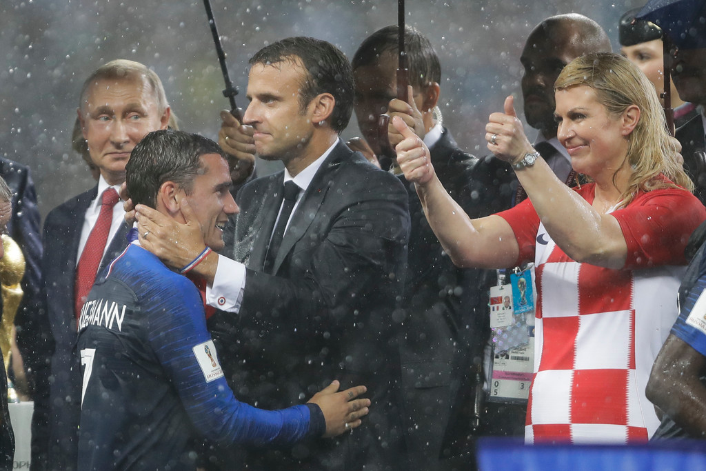 . France\'s President Emmanuel Macron embraces Antoine Griezmann as Croatia\'s President Kolinda Grabar-Kitarovic makes a thumb up during the awards ceremony after the final match between France and Croatia at the 2018 soccer World Cup in the Luzhniki Stadium in Moscow, Russia, Sunday, July 15, 2018. (AP Photo/Natacha Pisarenko)