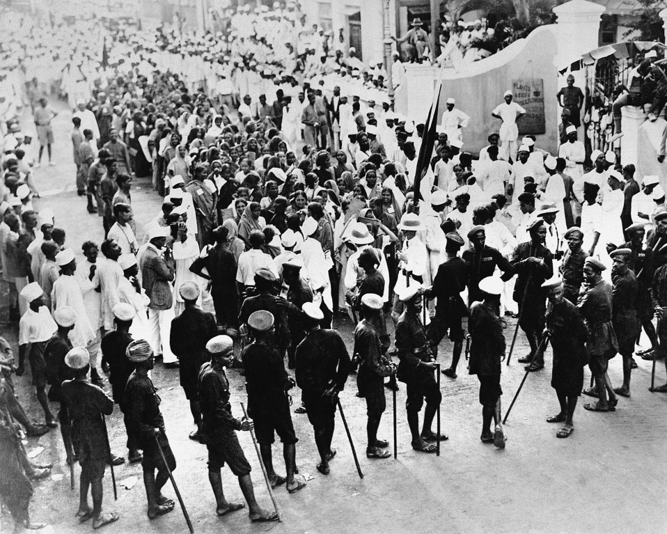 ". Police block an outlawed procession in front of the Nationalists\' Congress headquarters in Bombay, July 5, 1930, on the ground that it was in celebration of ""defiance of authority\"" in the Sholapur riots when fourteen people were killed. The native police, Mahratties, are shown in the foreground with their lathies or sticks of bamboo. Two European police sergeants, wearing helmets, are seen near the Gandhi flag. (AP Photo/J.P. Howe)"