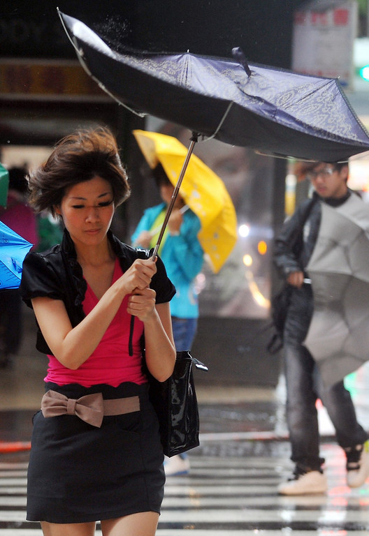 . A woman walks through strong winds and rain caused by Typhoon Fitow in Taipei on October 6, 2013. Taiwan on October 5 issued a warning over Typhoon Fitow as it approached the island\'s north with threats of torrential rains and powerful winds over the weekend.  Mandy Cheng/AFP/Getty Images