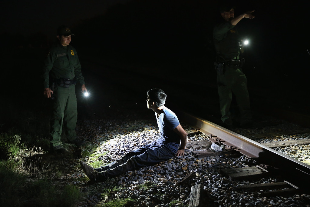 . U.S. Border Patrol agents detain an undocumented immigrant along a railroad track near the Rio Grande River at the U.S.-Mexico border on September 8, 2014 near McAllen, Texas. (Photo by John Moore/Getty Images)