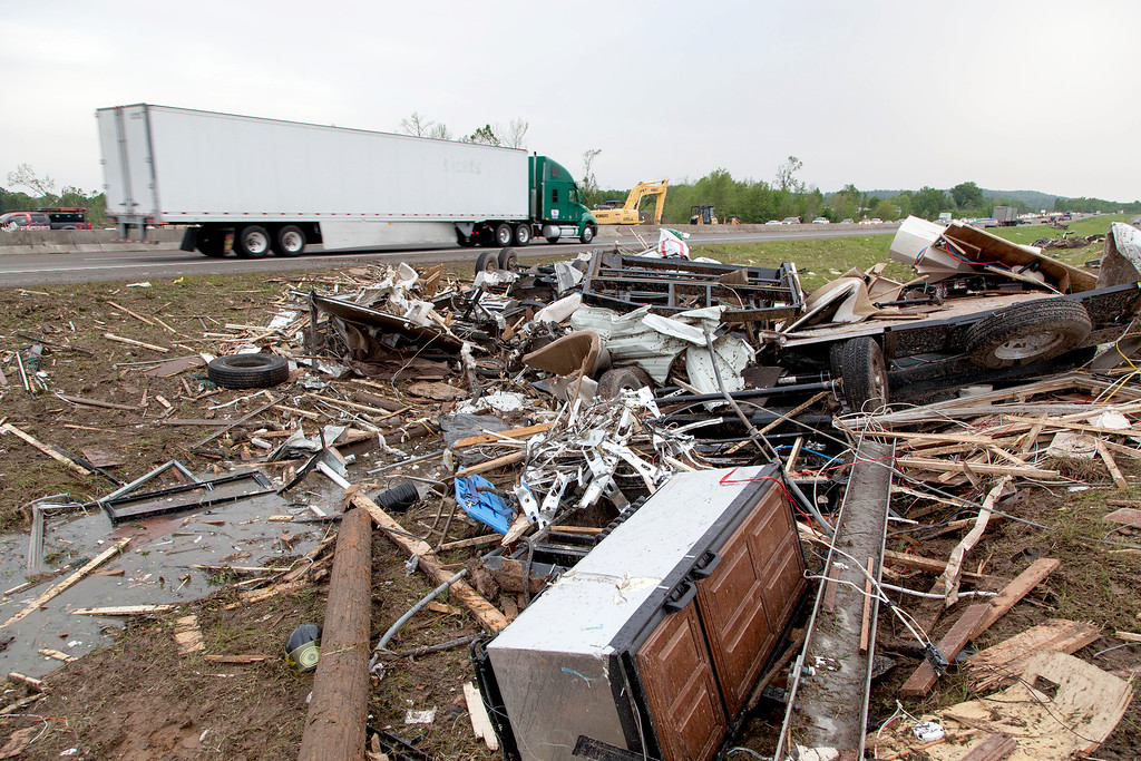 . Piles of debris sits along side of Interstate 40 westbound as traffic flows slowly Monday, April 28, 2014 in Mayflower, Ark., after a tornado struck the town late Sunday. Mayflower was hit hard Sunday after a tornado system ripped through several states in the central U.S. and left more than a dozen dead in a violent start to this year\'s storm season, officials said.  (AP Photo/Karen E. Segrave)