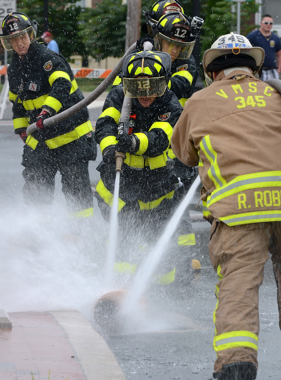 . Colmar Fire Company members and VMSC compete in a water battle demonstration for the Fairmount Fire Company 125th Anniversary festivities during the Lansdale Founders Day celebration on Saturday August 23,2014. Photo by Mark C Psoras/The Reporter