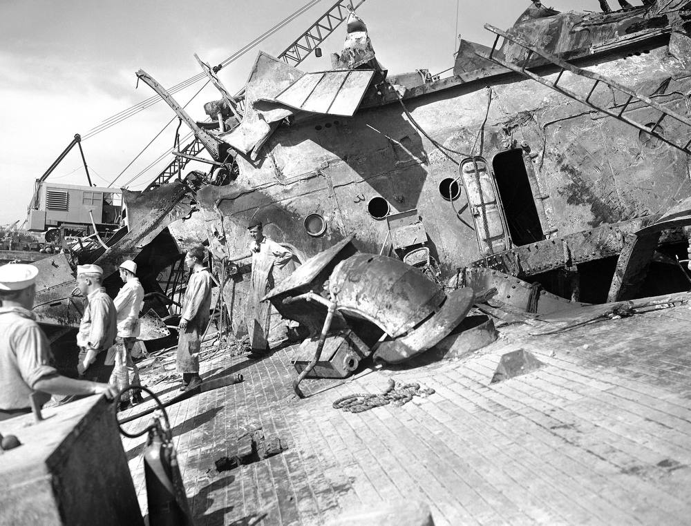. U.S. Navy salvage crews begin work of clearing wreckage from the decks of the U.S. Oklahoma in Pearl Harbor on May 23, 1943, sunk by Japanese bombs in opening attack of the war on Dec. 7, 1941. Huge crane in background removed much of twisted wreckage. Hose beside the men\'s feet is for pumping water from inside the ship. (AP Photo)