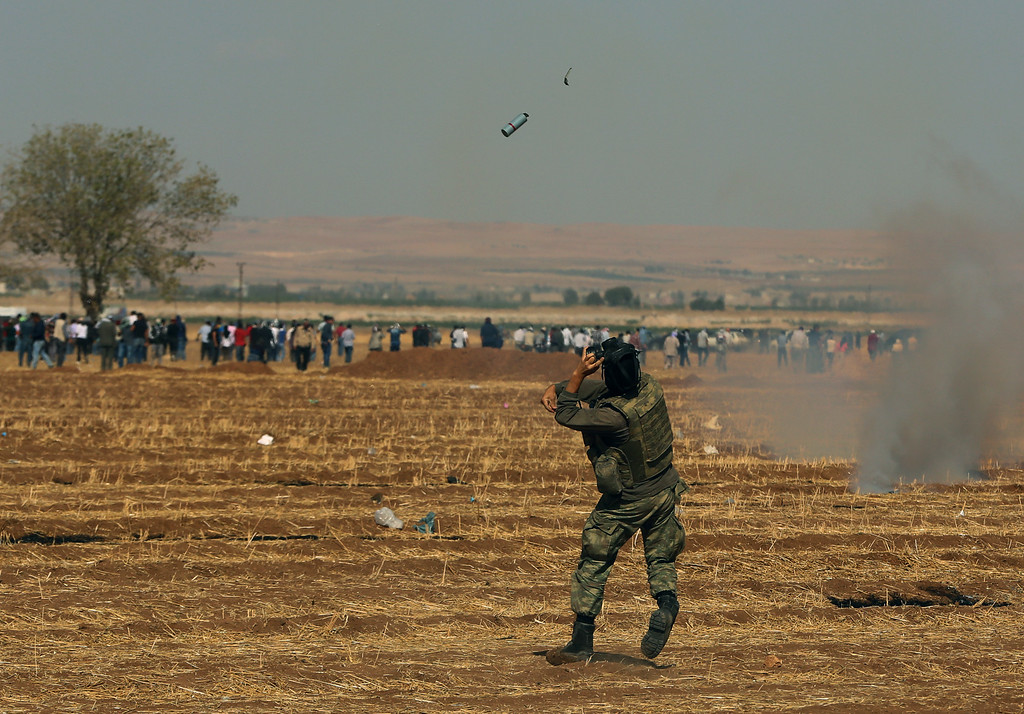 . A Turkish soldier throws a teargas canister towards Kurdish demonstrators, during clashes,  as thousands of Syrian refugees continue to arrive at the border in Suruc, Turkey, Monday, Sept. 22, 2014.  (AP Photo/Burhan Ozbilici)