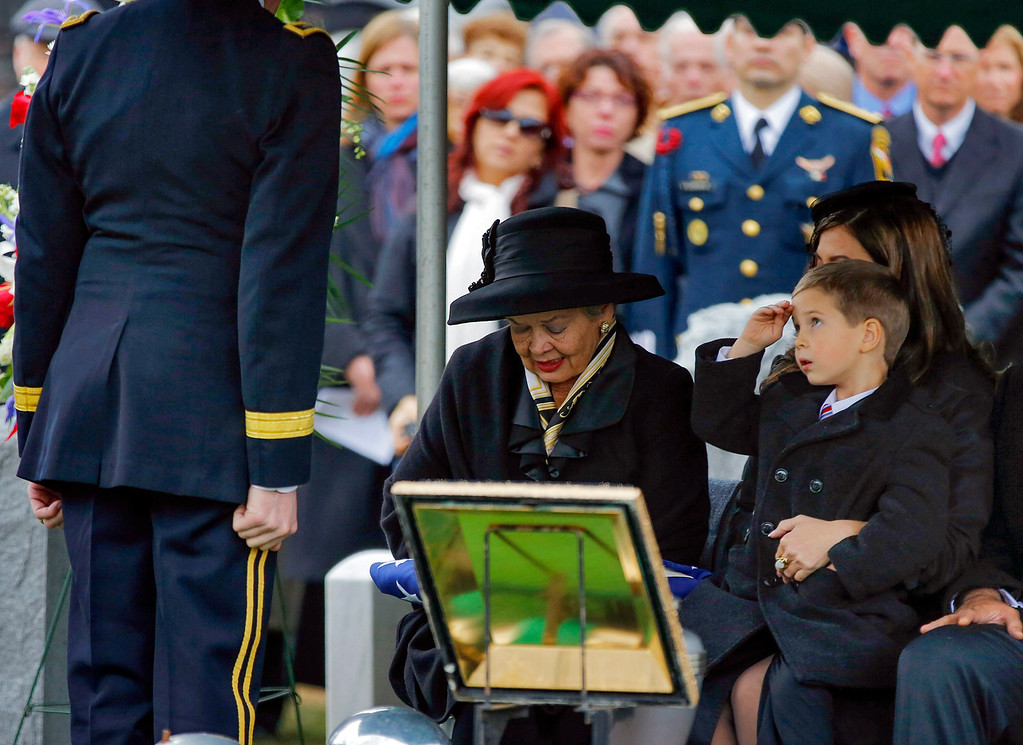 . Max Karmazyn, right, sitting next to his grandmother Brenda Schwarzkopf, left, salutes during the burial of his late grandfather, Gen. Norman Schwarzkopf,  at the United States Military Academy on Thursday, Feb. 28, 2013, in West Point, N.Y.  (AP Photo/Philip Kamrass)
