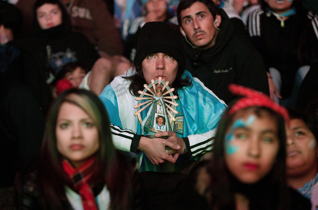. An Argentina soccer fan holds a statue of the Virgin Mary and a portrait of player Lionel Messi as he gathers with others to watch their team\'s World Cup match with Bosnia on an outdoor screen in Buenos Aires, Argentina, Sunday, June 15, 2014. (AP Photo/Eduardo Di Baia)