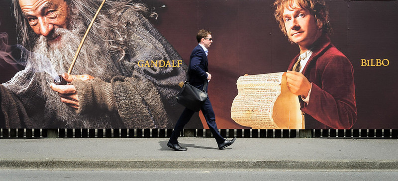 . A man walks along a fence hung with large format hoardings of J. R. R. Tolkien characters from The Hobbit movie in Wellington November 27, 2012. New Zealand\'s capital city was rushing to complete its transformation into a haven for hairy feet and pointed ears on Tuesday as stars jetted in for the long-awaited world premiere of the first movie of the Hobbit trilogy. REUTERS/Mark Coote