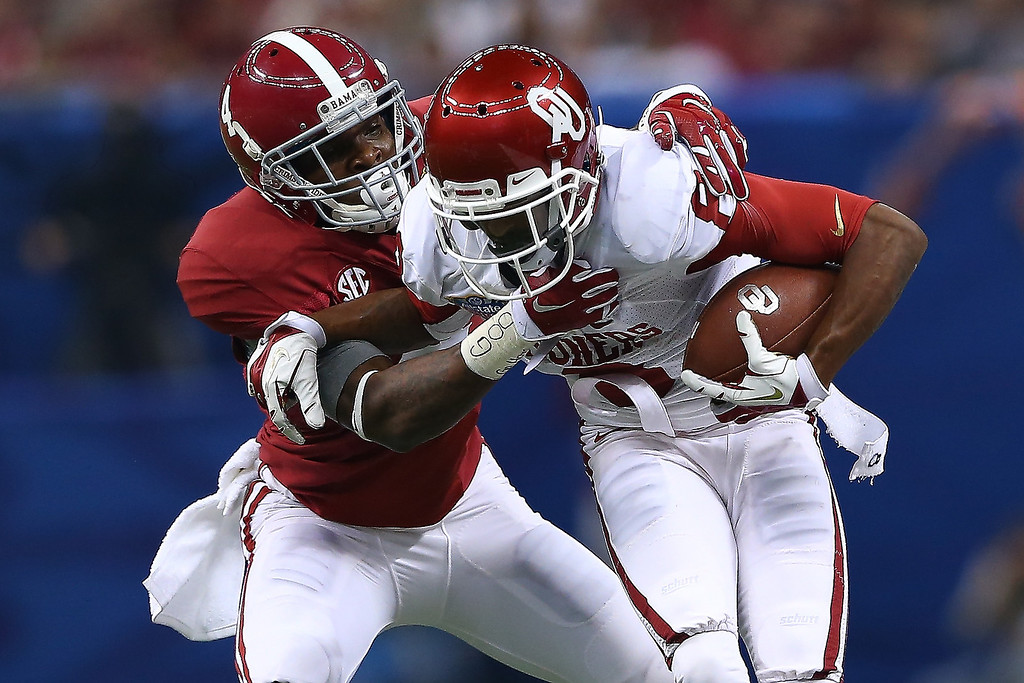 . NEW ORLEANS, LA - JANUARY 02:  Jalen Saunders #8 of the Oklahoma Sooners is tackled by Eddie Jackson #4 of the Alabama Crimson Tide during the Allstate Sugar Bowl at the Mercedes-Benz Superdome on January 2, 2014 in New Orleans, Louisiana.  (Photo by Streeter Lecka/Getty Images)