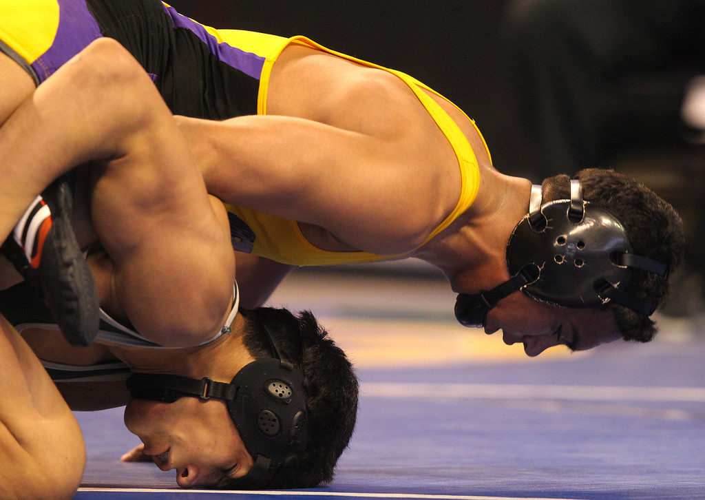 . Riordan\'s Zac Contreras, top, wrestles Poway\'s Victor Lopez in a 145-pound third place match during the California Interscholastic Federation wrestling championships in Bakersfield, Calif., on Saturday, March 2, 2013. Lopez would go onto win the match. (Anda Chu/Staff)