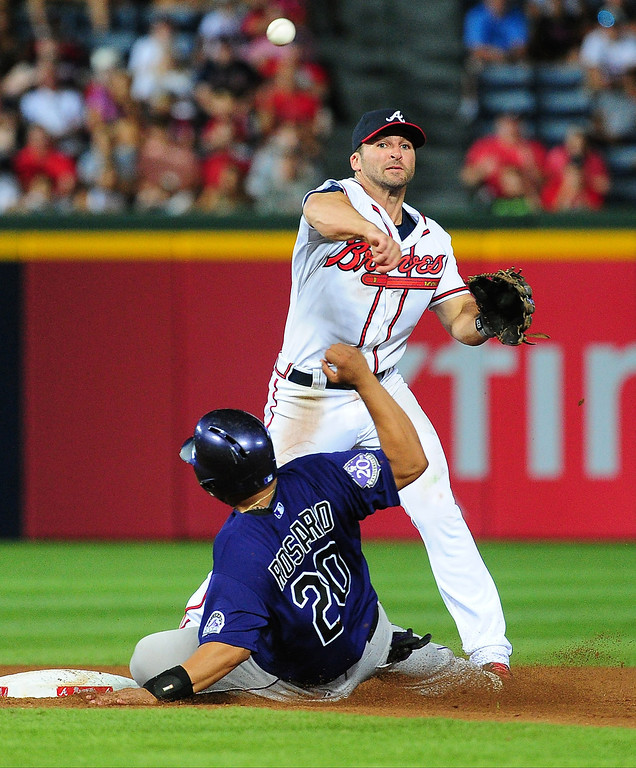 . Dan Uggla #26 of the Atlanta Braves turns a double play against Wilin Rosario #20 of the Colorado Rockies at Turner Field on July 29, 2013 in Atlanta, Georgia. (Photo by Scott Cunningham/Getty Images)