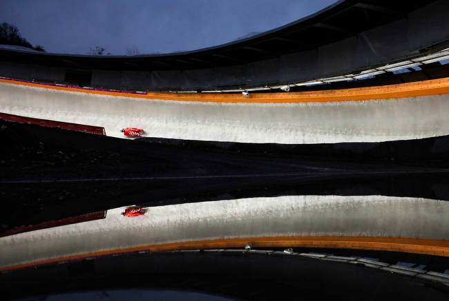 . An Austrian athlet competes in the men\'s training race at the Sliding Center Sanki during the the Luge World Cup 2013, in Krasnaya Polyana resort, some 60 kilometers (37 miles) east of Sochi, Russia, Friday, Feb. 22, 2013, reflecting in a puddle of rain. (AP Photo/Alexander Zemlianichenko)