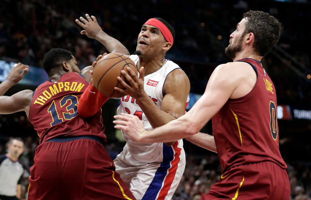 . Detroit Pistons\' Tobias Harris, center, drives between Cleveland Cavaliers\' Tristan Thompson, left, and Kevin Love in the second half of an NBA basketball game, Sunday, Jan. 28, 2018, in Cleveland. The Cavaliers won 121-104. (AP Photo/Tony Dejak)