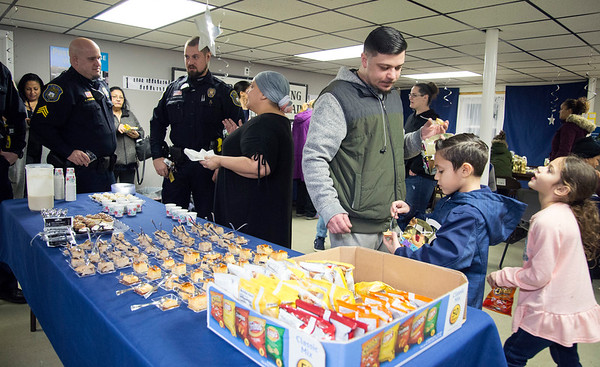 01/06/19 Wesley Bunnell | StaffrrThree Kings Day was celebrated at Neighborhood Services of New Britain at 223 Broad St for families on Monday night. Richard Walas, 4th L, looks over desserts with his son Jackson Richard Walas, age 7 , and daughter Cosima Walas, age 6. Idalis Moreno, 3rd L, chats with officers from the NBPD who visited the celebration.