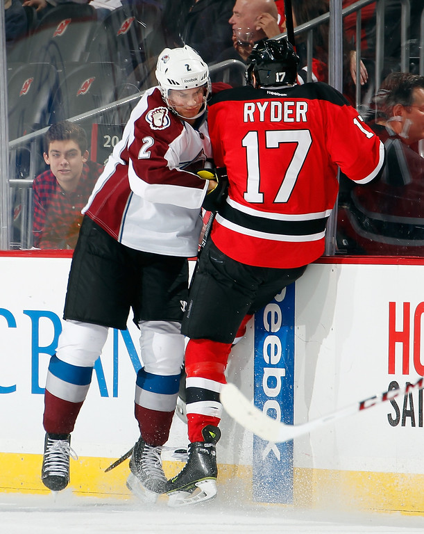 . Nick Holden #2 of the Colorado Avalanche checks Michael Ryder #17 of the New Jersey Devils during the third period in an NHL hockey game at Prudential Center on February 3, 2014 in Newark, New Jersey.  Colorado won 2-1 in overtime.  (Photo by Paul Bereswill/Getty Images)
