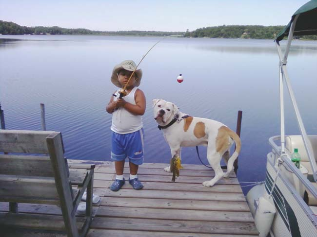 . Writes CINDY: �This is a picture of my grandson, Duncan, and his dog, Chopper Lee, fishing up at our cabin. This picture was taken over the Fourth of July weekend. (Duncan turned 4 on July 6th). His dog, Choppers, has to be tied up when Duncan fishes; otherwise, Choppers jumps in after the bobber.�