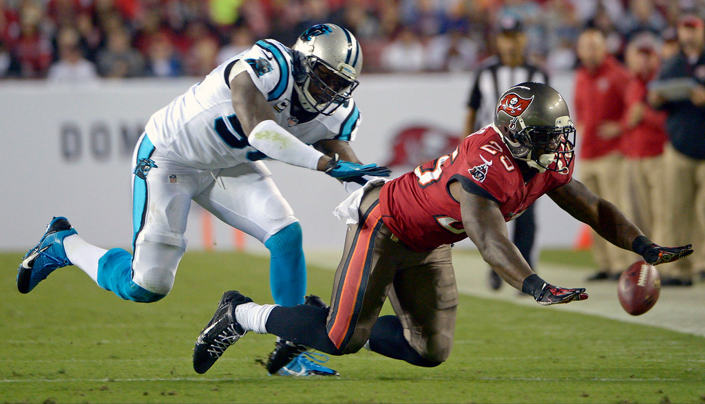 . Tampa Bay Buccaneers running back Mike James, right, cannot hang on to a pass as he is guarded by Carolina Panthers outside linebacker Thomas Davis, left, during the first half of an NFL football game in Tampa, Fla., Thursday, Oct. 24, 2013. (AP Photo/Phelan M. Ebenhack)