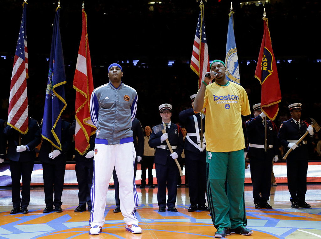. New York Knicks forward Carmelo Anthony, left, listens as Boston Celtics forward Paul Pierce speaks about the Boston Marathon bombings in front of color guards from New York and Boston  before Game 1 in the first round of the NBA basketball playoffs at Madison Square Garden in New York, Saturday, April 20, 2013.  (AP Photo/Kathy Willens)