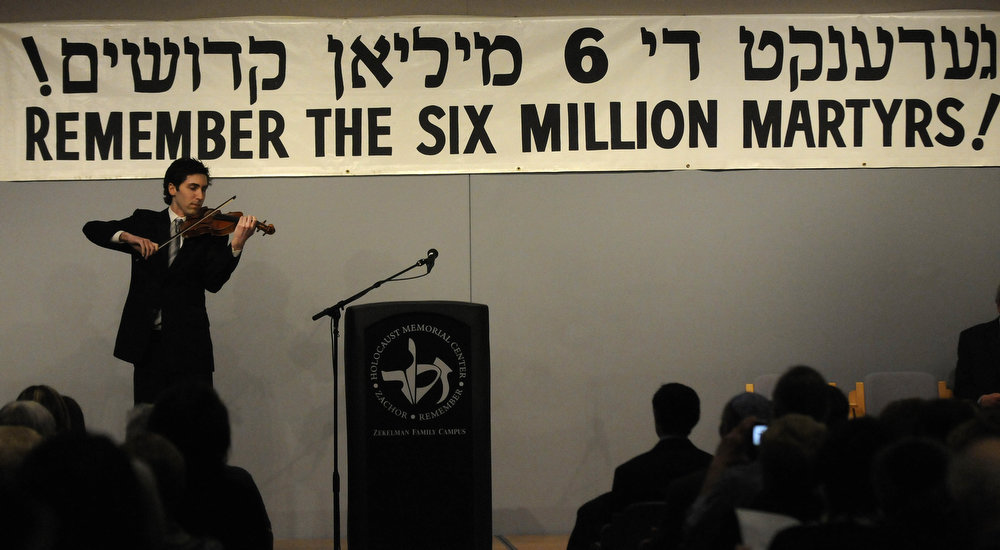 ". Jordan Allen Broder performs ""Yih\'yu L\'ratzon\"" or \""May the Words\"" on the violin during the beginning of  Yom HaShoah, a Holocaust Day of Remembrance, at the Holocaust Memorial Center in Farmington Hills, Mich., on Sunday, April 7, 2013. (AP Photo/Detroit News, Elizabeth Conley)"