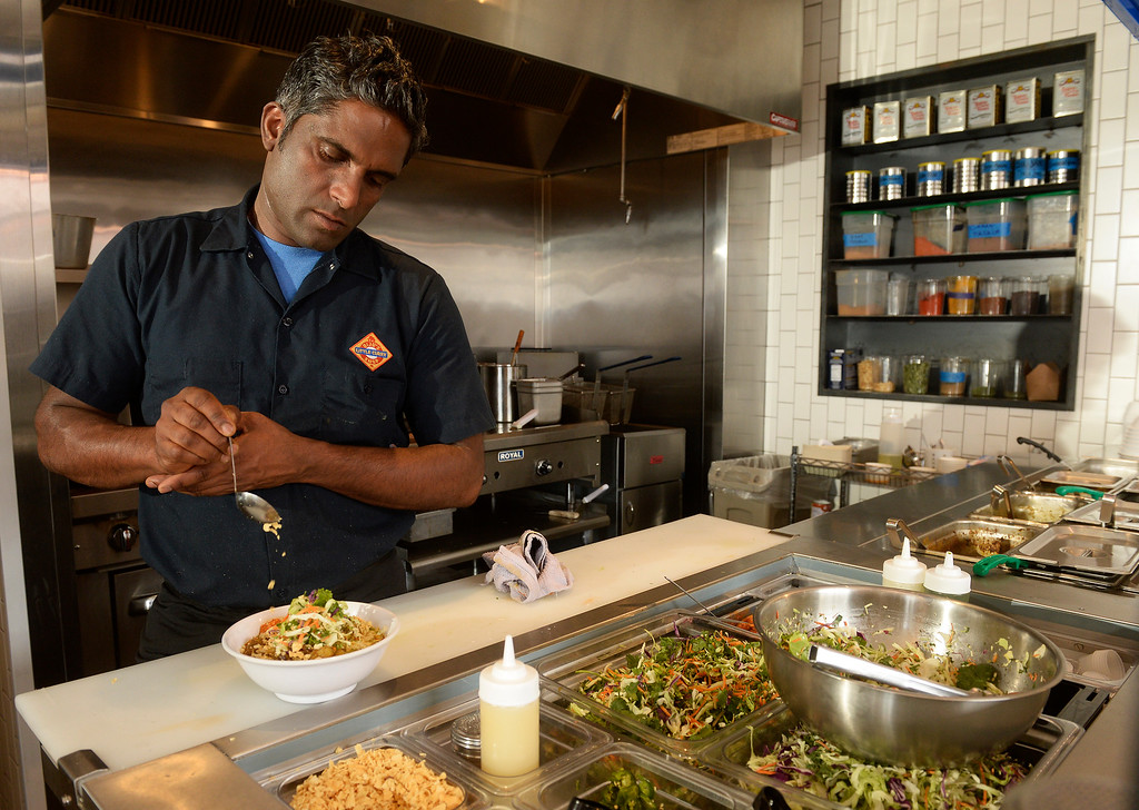 . Chef owner Biju Thomas  applies the finishing touches as he prepares a beef curry bowl at Biju\'s Little Curry Shop  in Denver. They serve southern Indian style veggie,  chicken or beef curry bowls.  The new restaurant  at 1441 26th Street,was photographed on Thursday, March 26, 2015.   (Photo by Cyrus McCrimmon/The Denver Post )