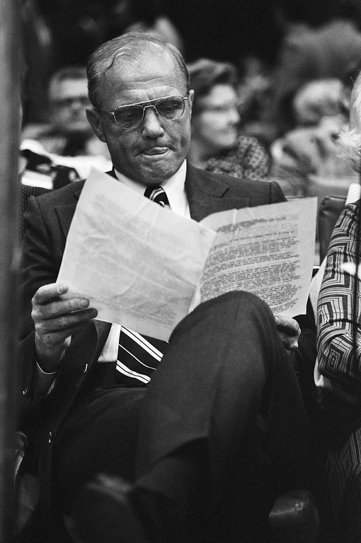 . Senator-elect John Glenn of Ohio bites his tongue as he studies some papers while attending the 1974 Democratic Mid-Term conference in Kansas City on Friday, Dec. 7, 1974. (AP Photo)