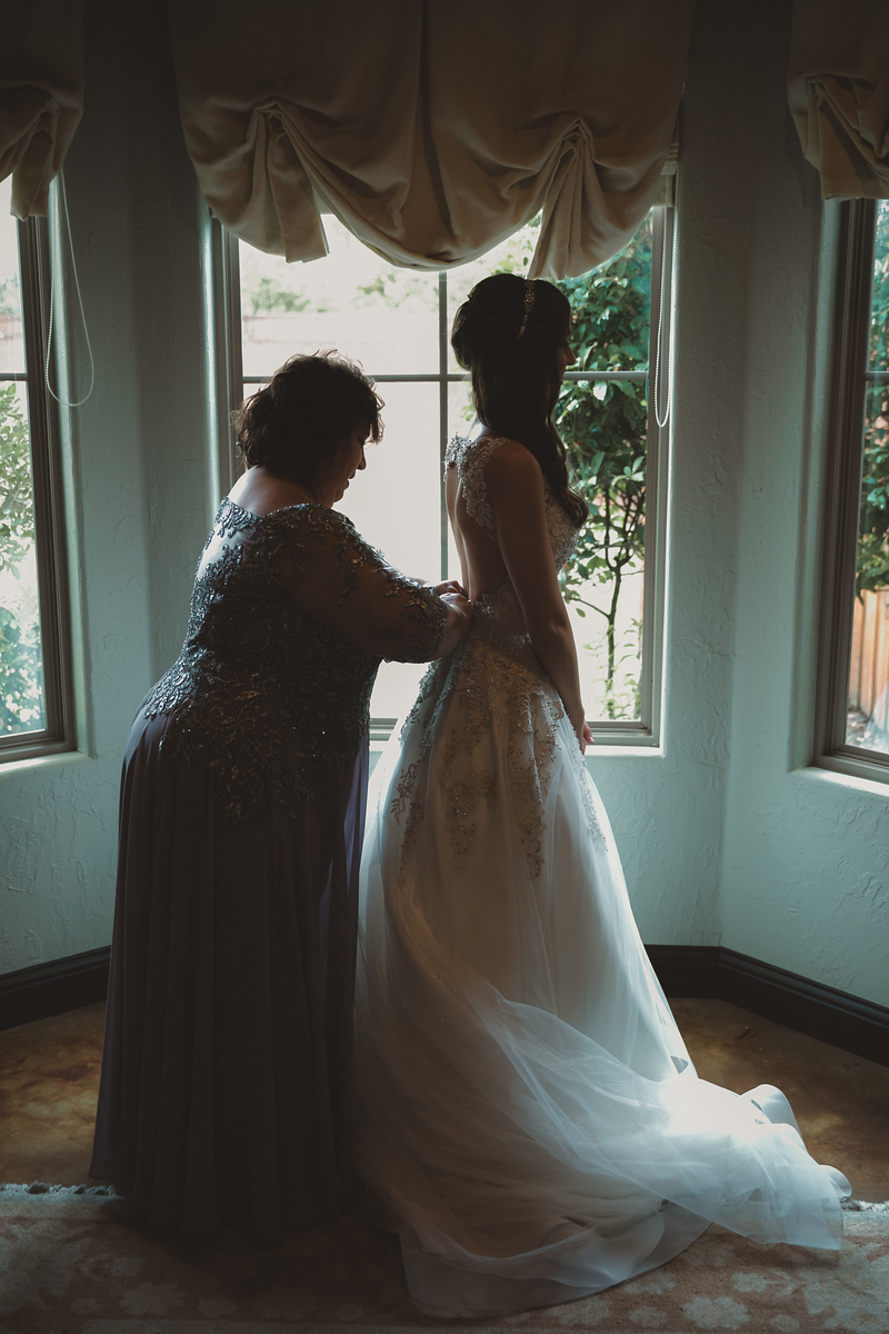 a brides mother zipping up her dress shortly before her wedding in front of a beautiful window setting at her wedding venue