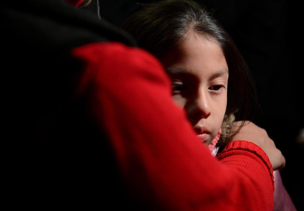 Description of . Cynthia Alvarez (R) is comforted by her mother Lilia as people gather for a prayer vigil at St Rose Church following an elementary school shooting in Newtown, Connecticut, December 14, 2012.  A young gunman slaughtered 20 small children and six teachers on Friday after walking into a school in an idyllic Connecticut town wielding at least two sophisticated firearms. EMMANUEL DUNAND/AFP/Getty Images