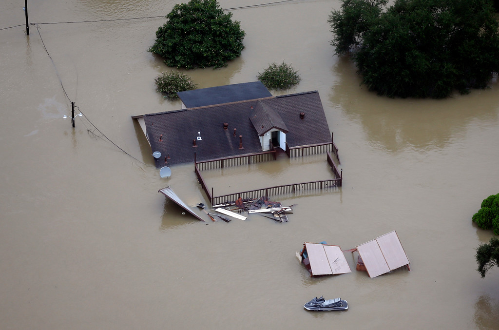 . A home is surrounded by floodwaters from Tropical Storm Harvey Tuesday, Aug. 29, 2017, in Houston. (AP Photo/David J. Phillip)