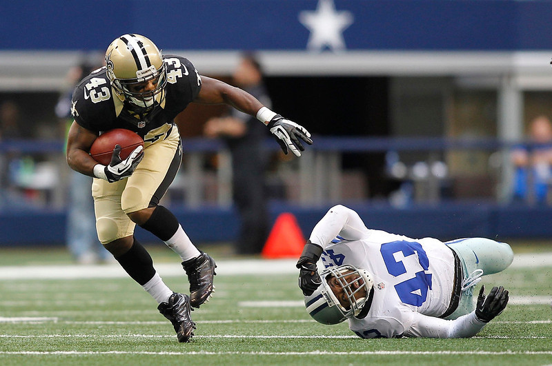 . New Orleans Saints running back Darren Sproles (L) breaks from Dallas Cowboys safety Gerald Sensabaugh in the first half of their NFL football game in Arlington, Texas December 23, 2012.  REUTERS/Mike Stone