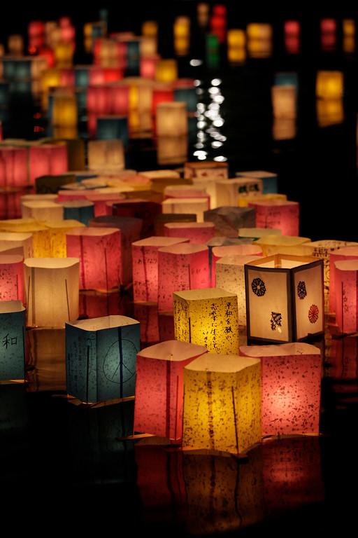 . Paper lanterns float along the Motoyasu River that runs by the Atomic Bomb Dome in Hiroshima, western Japan, Tuesday, Aug. 6, 2013.  (AP Photo/Shizuo Kambayashi)