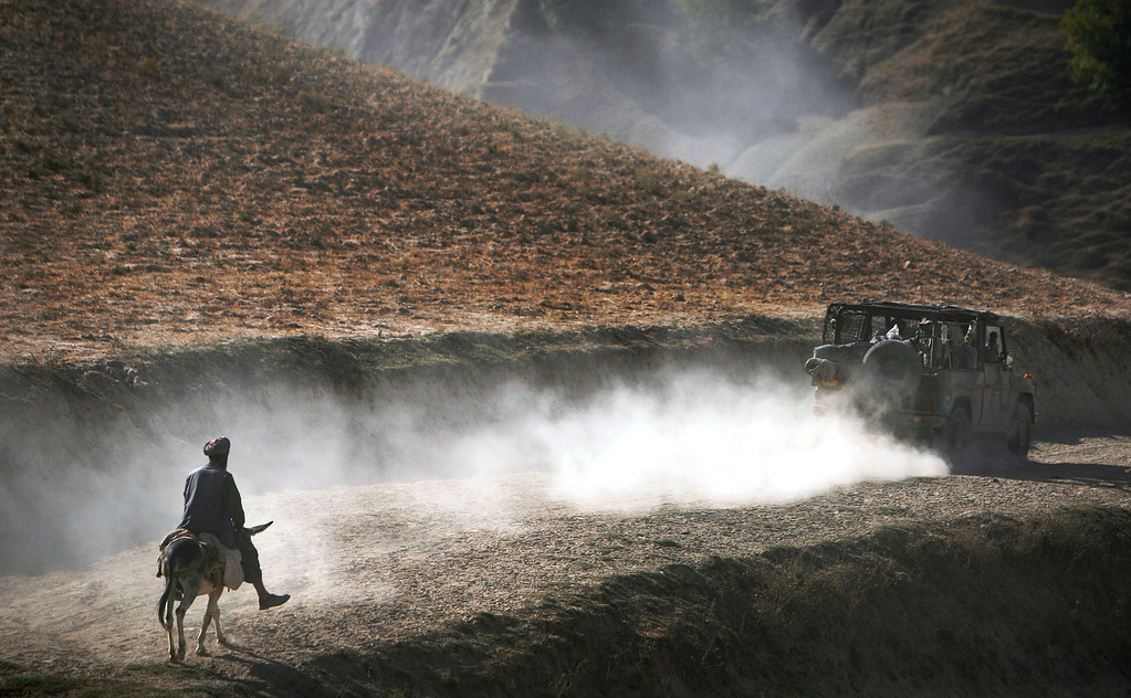 . In this Tuesday, Sept. 15, 2009 file photo, an Afghan man on his donkey follows a convoy of German ISAF soldiers patrolling Yaftal E Sofla, in the mountainous region of Feyzabad, east of Kunduz, Afghanistan.  (AP Photo/Anja Niedringhaus, File)