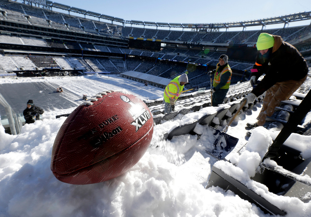 . A football with the Super Bowl XLVIII logo is set on a mound of snow for an NFL photographer to make photos of it as workers shovel snow off the seating area at MetLife Stadium as crews removed snow ahead of Super Bowl XLVIII following a snow (AP Photo/Julio Cortez)