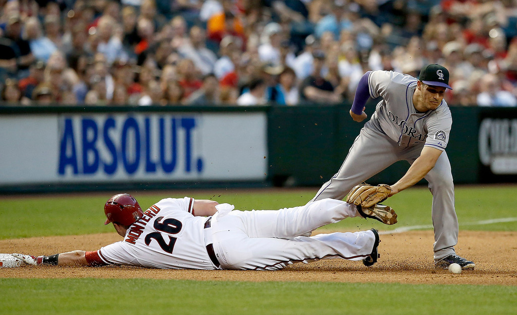 . Arizona Diamondbacks\' Miguel Montero (26) dives safely into third base as Colorado Rockies\' Nolan Arenado is unable to catch the ball during the second inning of a baseball game on Tuesday, April 29, 2014, in Phoenix. (AP Photo/Ross D. Franklin)