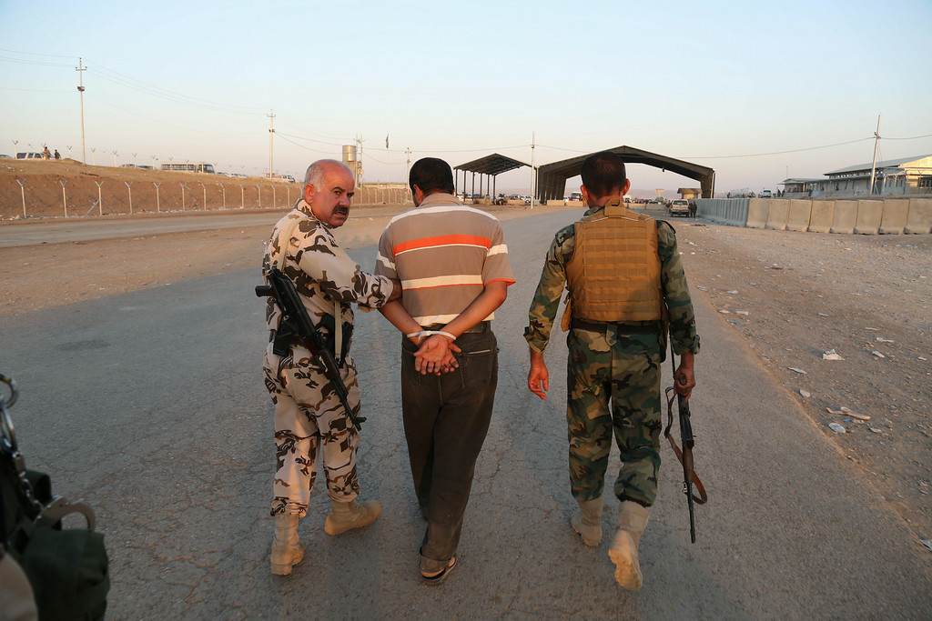 . Kurdish Peshmerga fighters detain a man suspected as a militant for the Islamic State group, as airstrikes target Islamic State militants near the Khazer checkpoint outside of the city of Irbil in northern Iraq, Friday, Aug. 8, 2014.  (AP Photo/Khalid Mohammed)
