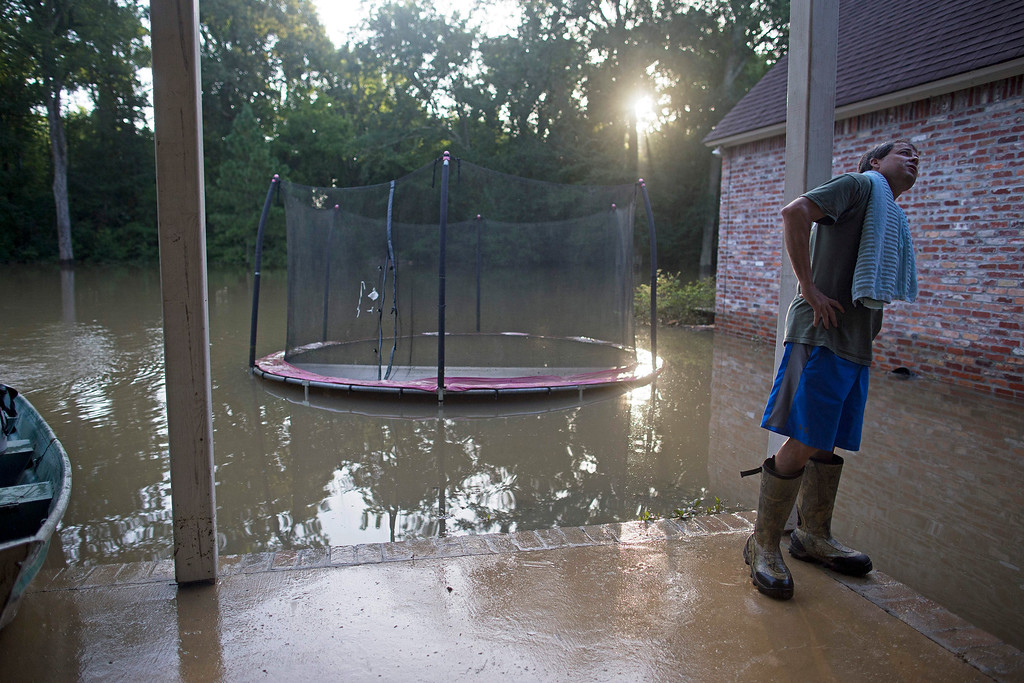 . David Key looks at the back yard of his flooded home in Prairieville, La., Tuesday, Aug. 16, 2016. Key, an insurance adjuster, fled his home as the flood water was rising with his wife and three children and returned today to assess the damage. (AP Photo/Max Becherer)