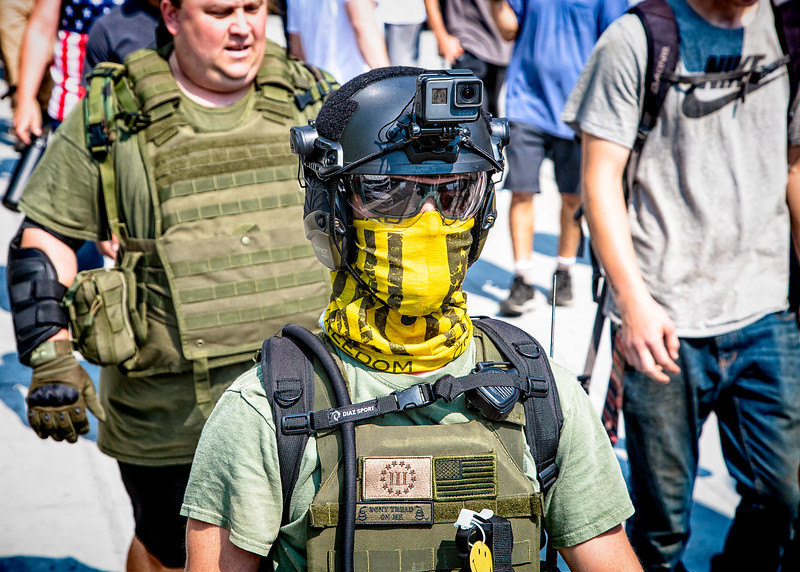A right wing supporter, concealing his face with a yellow bandanna, is ready to film the action with a GoPro camera strapped to his helmet.