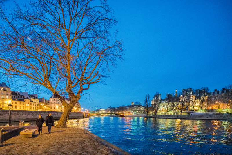 A couple walking by the Seine river on Saint Louis island, Paris, France