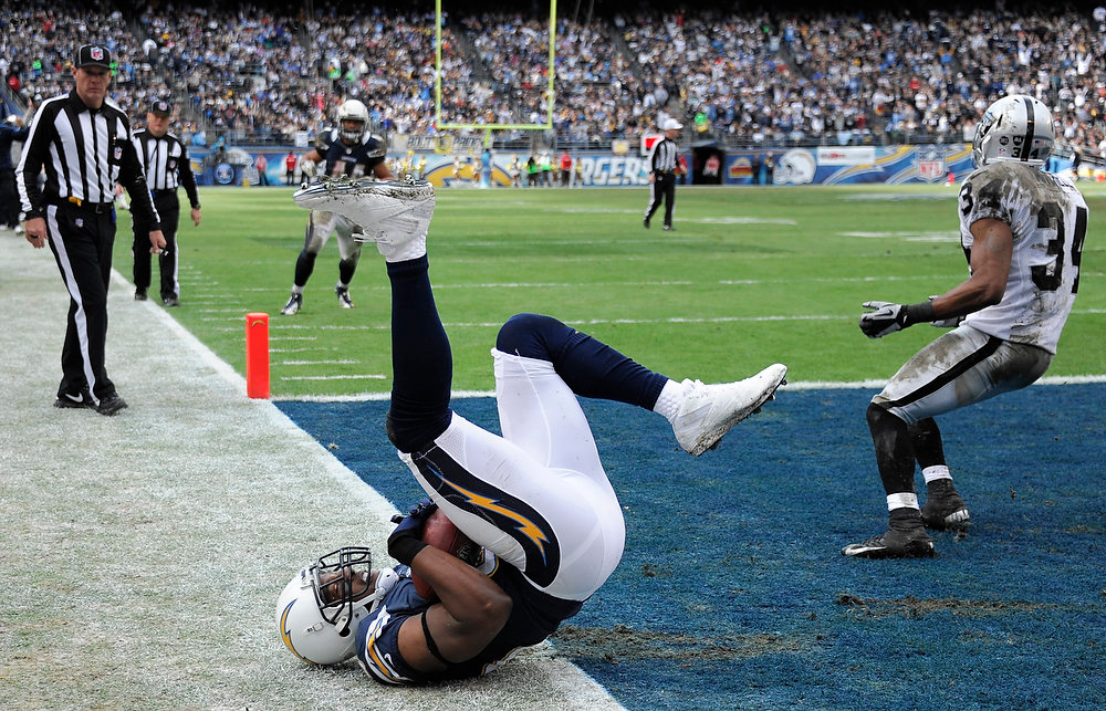Description of . San Diego Chargers tight end Antonio Gates rolls after scoring a touchdown as Oakland Raiders strong safety Mike Mitchell, right, looks back during the first half of an NFL football game Sunday, Dec. 30, 2012, in San Diego. (AP Photo/Denis Poroy)